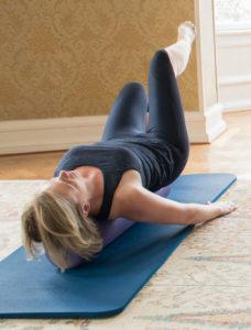 kvinna tränar på matta med rulle